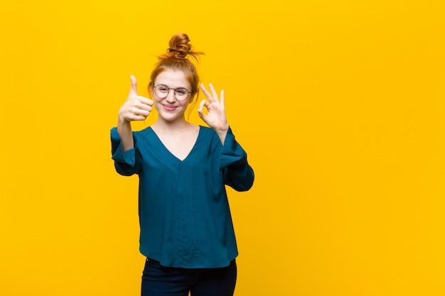 Молодая рыжеволосая женщина чувствует себя счастливой, изумленной, удовлетворенной и удивленной, показывает нормально и недурно жестами, улыбается над оранжевой стеной