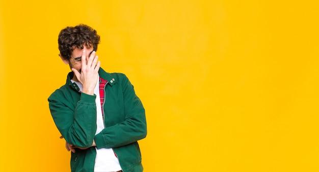 Молодой сумасшедший бородатый мужчина, выглядящий напряженным, стыдным или расстроенным, с головной болью, закрывающий лицо рукой над стеной