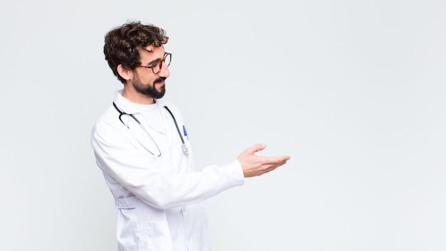 笑みを浮かべて、あなたに挨拶し、成功した取引を閉じるために手を振るを提供する若い医者男
