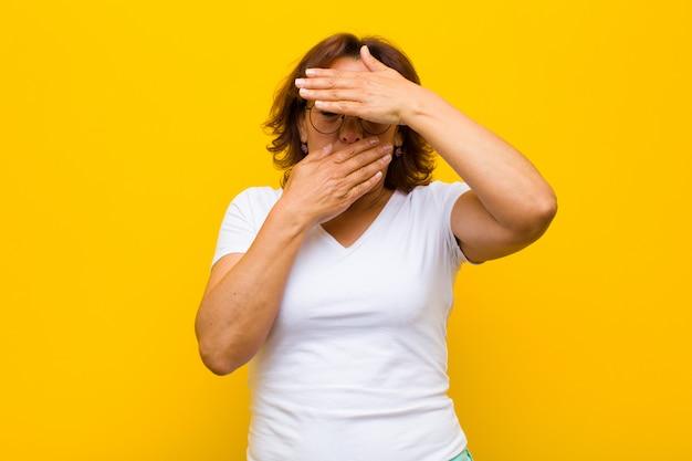 カメラにノーと言って両手で顔を覆っている中年女性!写真を拒否するか、黄色の壁を越えて写真を禁止する