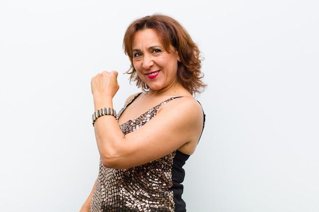 Симпатичная женщина среднего возраста чувствует себя счастливой, позитивной и успешной, мотивированной, когда сталкивается с проблемой или празднует хорошие результаты за белой стеной