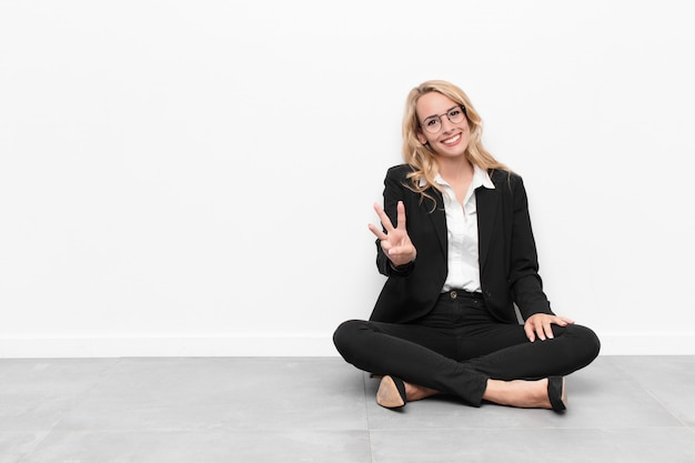 コピースペースでセメントの床に座っている若い金髪の実業家
