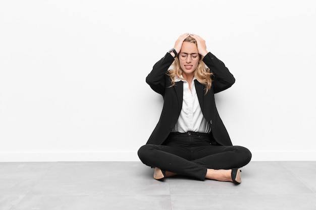 Молодая блондинка, чувствуя стресс и беспокойство, депрессию и разочарование от головной боли, поднимая обе руки к голове, сидя на полу