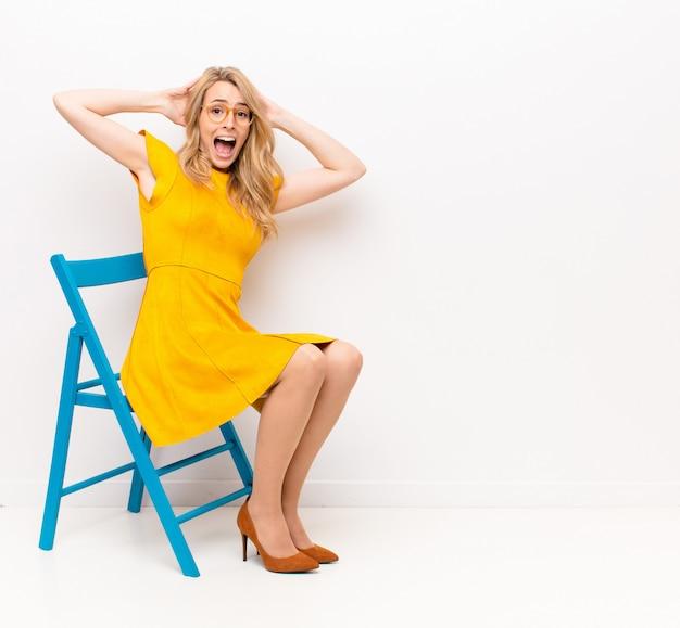 Молодая красивая белокурая женщина выглядит счастливой, беззаботной, дружелюбной и расслабленной, наслаждающейся жизнью и успехом, с позитивным отношением к цветной стене