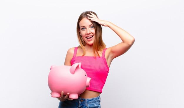 フレンドリーで自信を持って、肯定的な表情で喜んで笑って、貯金箱を提供し、示す赤い頭のきれいな女性