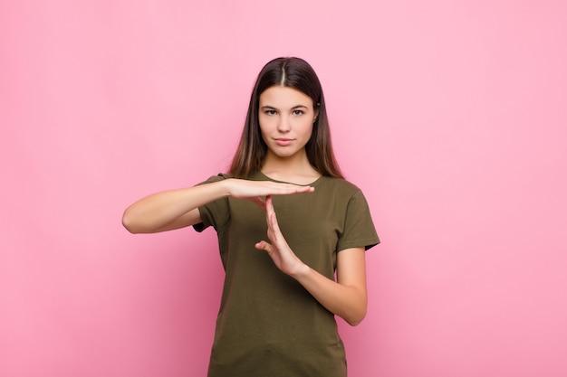 Молодая симпатичная женщина, выглядящая серьезной, строгой, злой и недовольной, делающей знак времени ожидания над розовой стеной