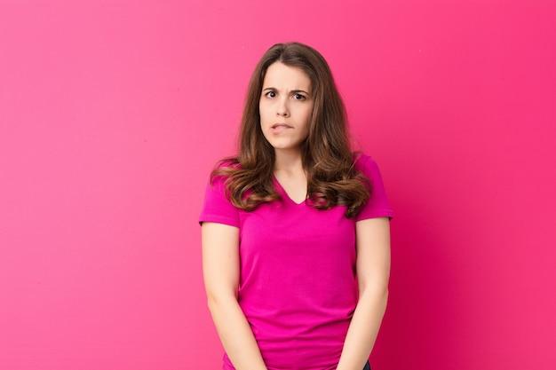 Молодая симпатичная женщина выглядит озадаченной и смущенной, кусая губу нервным жестом, не зная ответа на проблему над розовой стеной