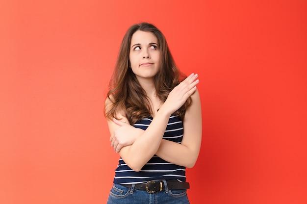 Молодая симпатичная женщина, чувствующая себя смущенной и невежественной, задается вопросом о сомнительном объяснении или обдумывает красную стену