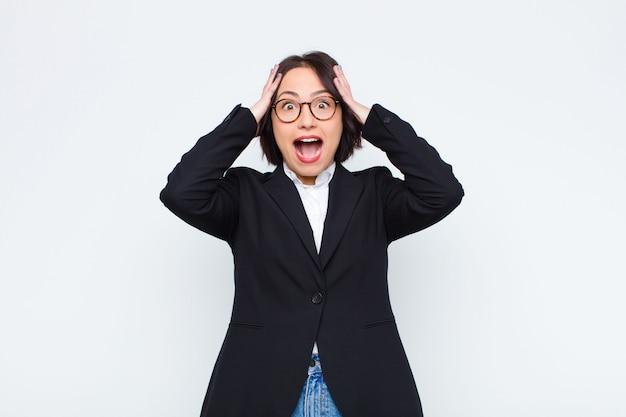 Молодая деловая женщина поднимает руки к голове, с открытым ртом, чувствуя себя чрезвычайно счастливой, удивленной, взволнованной и счастливой над белой стеной