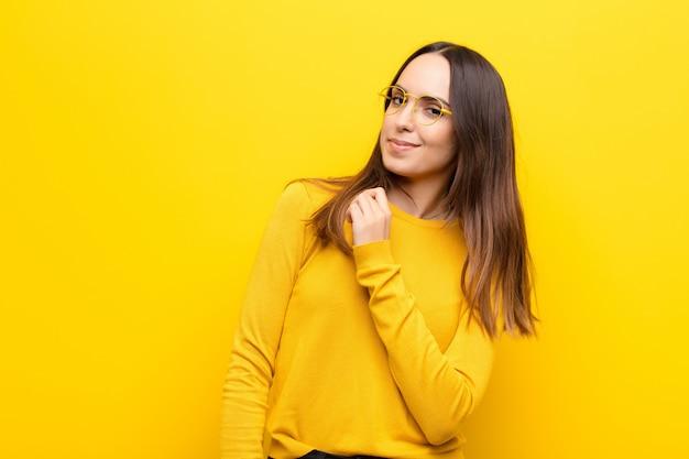 Молодая красивая женщина, глядя высокомерный, успешный, позитивный и гордый, указывая на себя над оранжевой стеной