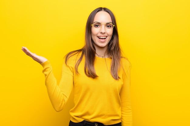 オレンジ色の壁の上のソリューションまたはアイデアを実現する幸せ、驚き、陽気、前向きな姿勢で笑顔を感じて若いきれいな女性