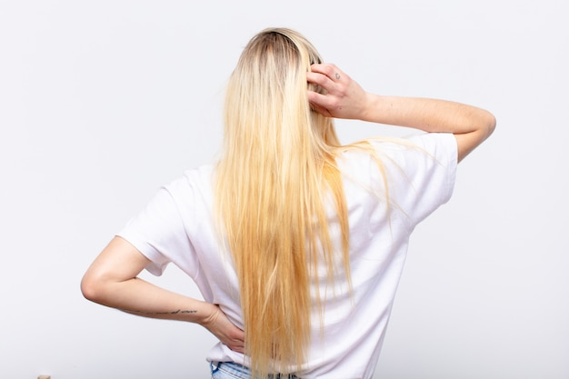 無知と混乱を感じて若いかなりブロンドの女性、解決策を考えて、腰と他の頭の上の手で、白い壁の背面図