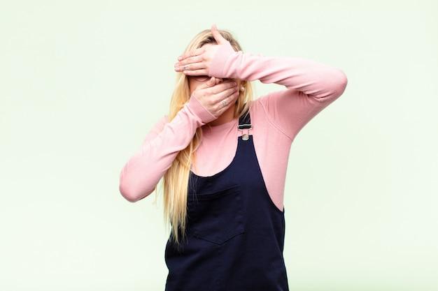 ノーと言って写真を拒否して両手で顔を覆っている若いかなりブロンドの女性