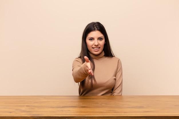 Молодая красивая женщина улыбается, приветствуя вас и предлагая дрожание рук, чтобы закрыть успешную сделку, концепция сотрудничества, сидя за столом
