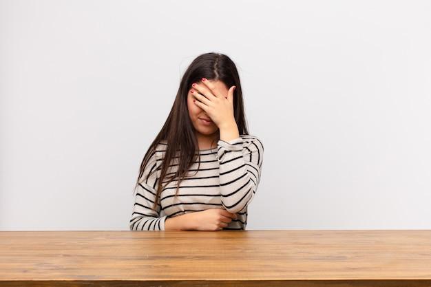 Молодая красивая женщина, глядя подчеркнул, стыдно или расстроен, с головной болью, закрыв лицо рукой, сидя за столом