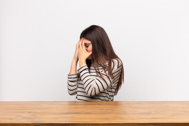 悲しい、欲求不満の絶望、泣き、テーブルに座っての側面図の手で目を覆っている若いきれいな女性