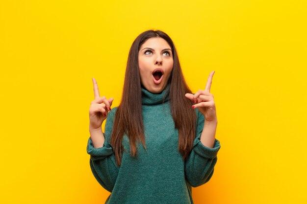 ショックを受けて、驚いて、口を開けて、黄色の壁を両手で上向きに見て若いきれいな女性