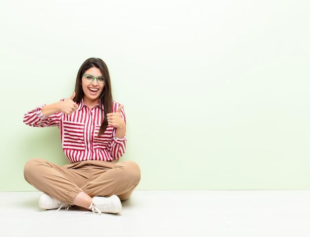 Молодая красивая женщина, широко улыбаясь, выглядит счастливой, позитивной, уверенной и успешной, с двумя большими пальцами, сидя на полу
