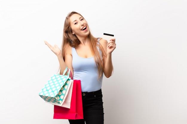 幸せ、驚き、陽気、前向きな姿勢で笑って、解決策を実現し、買い物袋を保持している若いブロンドの女性