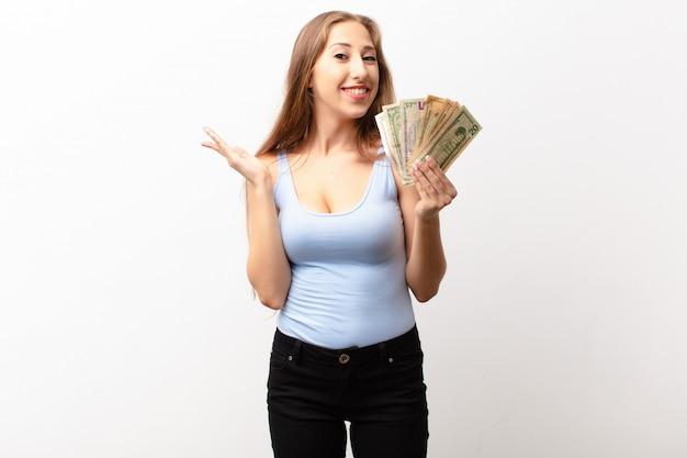 幸せ、驚き、陽気、前向きな姿勢で笑って、ドル紙幣を保持している解決策やアイデアを実現する若い金髪の女性