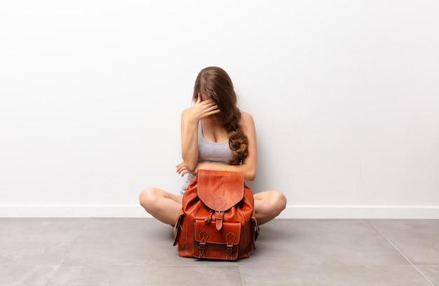 Молодая блондинка выглядит напряженно, стыдно или расстроена, с головной болью, закрывает лицо рукой, сидя на полу