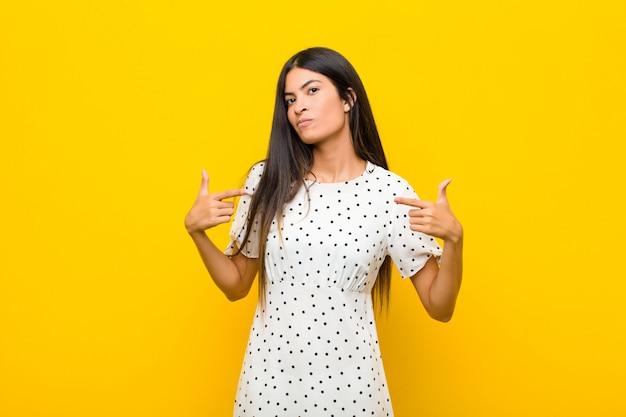 Молодая симпатичная латинская женщина выглядит гордой, высокомерной, счастливой, удивленной и удовлетворенной, указывая на себя, чувствуя себя победителем за стеной
