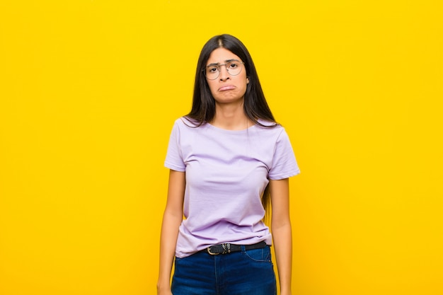 不幸な表情で悲しいと泣き言を感じ、壁を越えて否定的でイライラした態度で泣いている若いかなりラテン女性