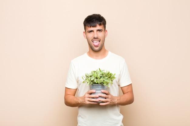 うんざりし、イライラし、舌を突き出し、植物を保持している厄介で不機嫌な何かを嫌う若いハンサムな男