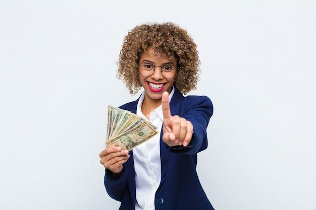 Молодая афроамериканская женщина, гордо и уверенно улыбающаяся, триумфально позирует номер один, чувствуя себя лидером с банкнотами евро