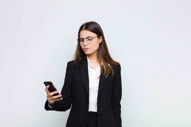 Молодая симпатичная женщина чувствует грусть, расстроен или зла и смотрит в сторону с негативным отношением, хмурится в несогласии с мобильным телефоном