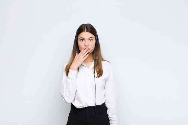 Молодая красивая женщина, охватывающих рот руками с шокирован, удивлен выражением, сохраняя в тайне или говоря ой с наушниками и микрофоном