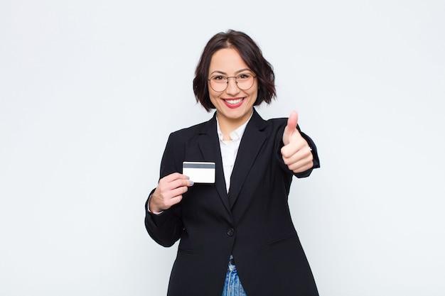 誇りに思って、屈託のない、自信を持って、幸せな、クレジットカードで親指で積極的に笑って若いきれいな女性