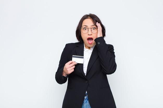 Молодая красивая женщина чувствует себя счастливым, взволнован и удивлен, глядя в сторону обеими руками на лицо с помощью кредитной карты
