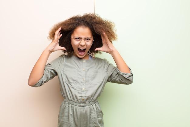 アフリカ系アメリカ人の少女が空中で手を叫んで、怒り、イライラ、ストレス、壁に動揺
