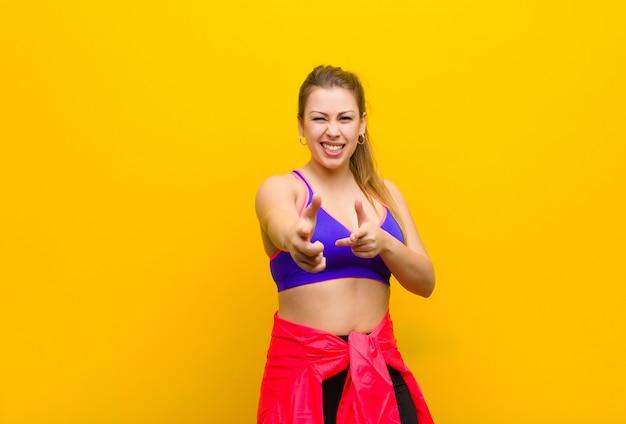 幸せ、クール、満足、リラックスして成功、ポインティング、スポーツコンセプトを選択する感じの若いブロンドの女性