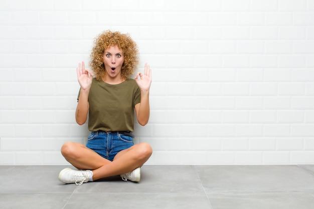 床に座って両方の手でいい兆候を作る承認を示すショックを受けて、驚いて、驚いた若い女性