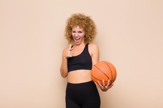 幸せ、クール、満足、リラックスして成功、ポインティング、スポーツコンセプトを選択する感じの若い女性