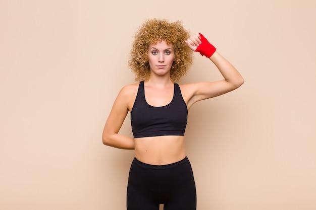Молодая женщина, чувствуя себя серьезной, сильной и непокорной, поднимая кулак вверх, протестуя или борясь за революционную спортивную концепцию