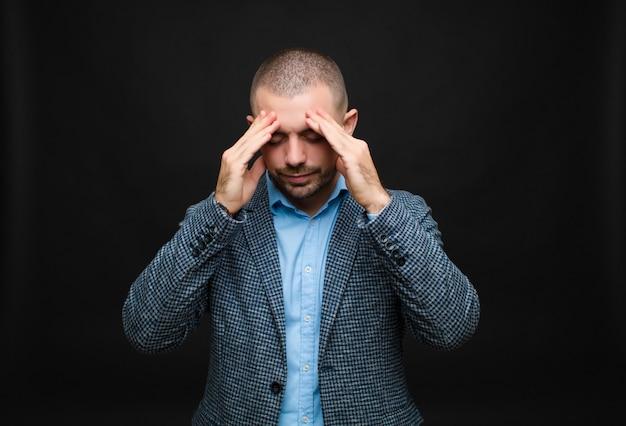 ストレスやイライラ、頭痛で圧力の下で働いて、壁を越えて問題に悩まされている青年実業家