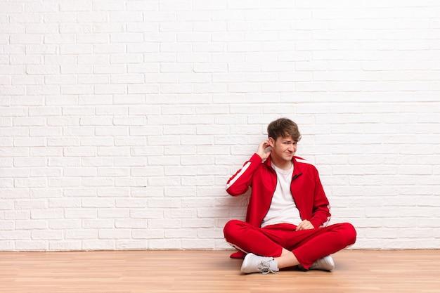 床に座って心配、問題を抱えた表情で、ストレス、イライラ、疲れ、痛みを伴う首をこする感じの若いブロンドの男