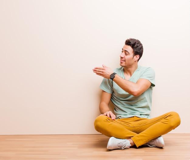 若い男は笑みを浮かべて、あなたに挨拶し、成功した取引、床に座って協力の概念を閉じるために手を振るを提供します