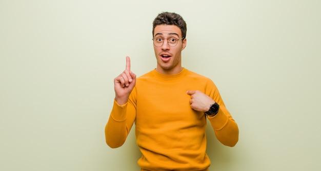 若い男は誇りと驚きを感じ、自信を持って自己を指し、壁を越えて成功したナンバーワンのような気分