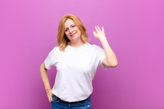 女性は喜んで元気よく笑って、手を振って、あなたを歓迎して挨拶、またはさようならを言って