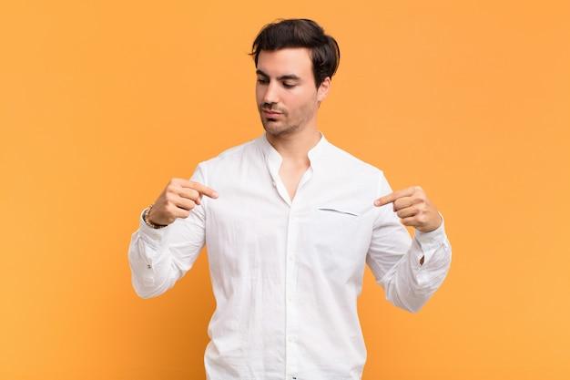 Молодой красивый мужчина, глядя гордый, позитивный и случайный, указывая на грудь обеими руками