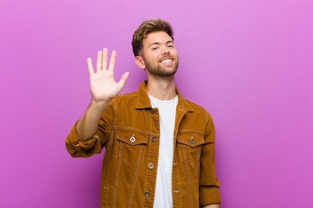 若い男が喜んで元気に笑って、手を振って、あなたを歓迎して挨拶、または紫色の壁に別れを告げる