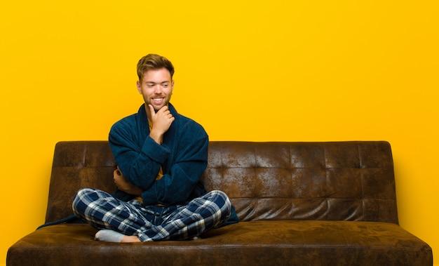 Пижамы молодого человека нося усмехаясь с счастливым, уверенно выражением с рукой на подбородке, интересуя и смотря к стороне. сидя на диване