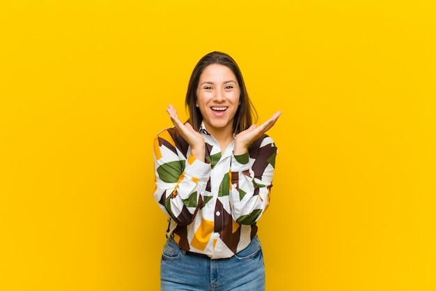 ラテンアメリカの女性は、黄色の壁に対して隔離された予期せぬ驚きのためにショックと興奮、笑い、驚きと幸せを感じて