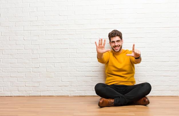 Молодой красавец, сидя на полу дома против текстуры кирпичной стены