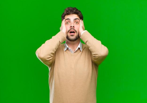 Молодой бизнесмен смотрит неприятно потрясен, напуган или обеспокоен, широко открыв рот и прикрывая оба уха руками у зеленой стены