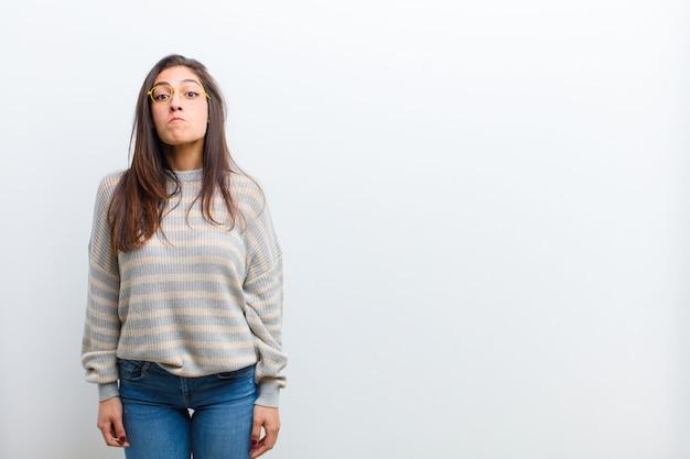 Молодая симпатичная женщина чувствует грусть и стресс, расстроена из-за плохого сюрприза, с негативным, тревожным взглядом, изолированным на белой стене